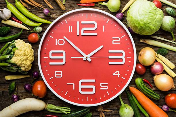 food clock. healthy food concept on wooden table - uhrenshop stock-fotos und bilder