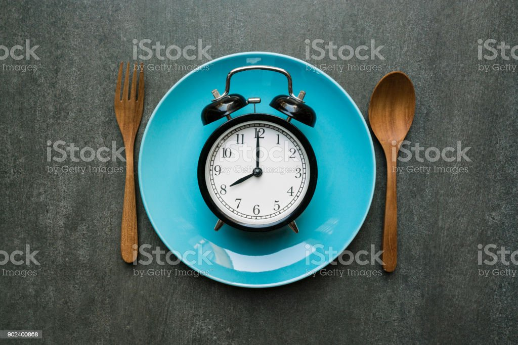 Food clock spoon and fork, Healthy food concept on black background stock photo
