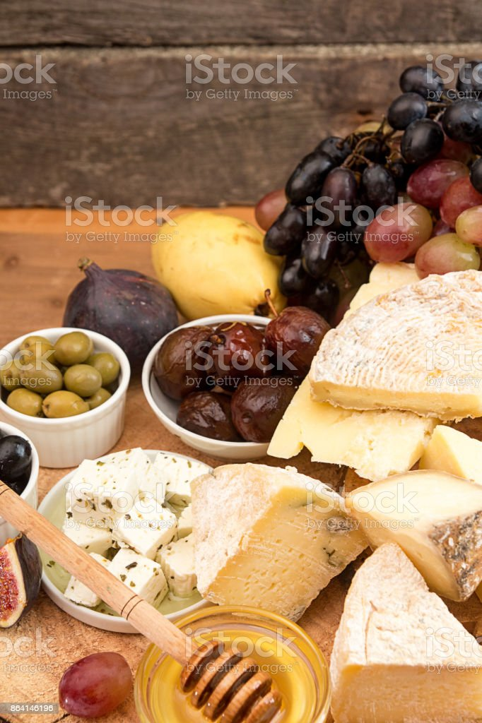 Food composition with blocks of moldy cheese, pickled plums, honey, grape bunch, olives, figs, pear, crackers, figs on old wooden background. royalty-free stock photo