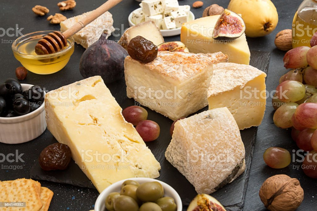 Food composition with blocks of moldy cheese, pickled plums, honey, grape bunch, olives, figs, crackers, figs on black background. royalty-free stock photo