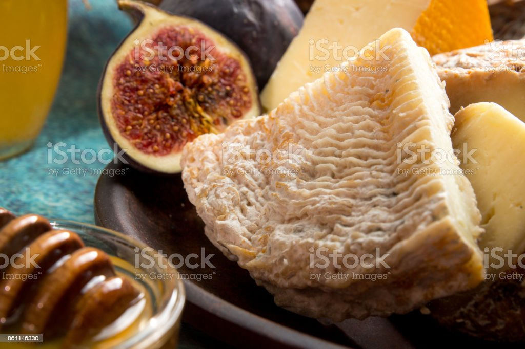 Food composition with piece of moldy cheese, honey, figs. royalty-free stock photo