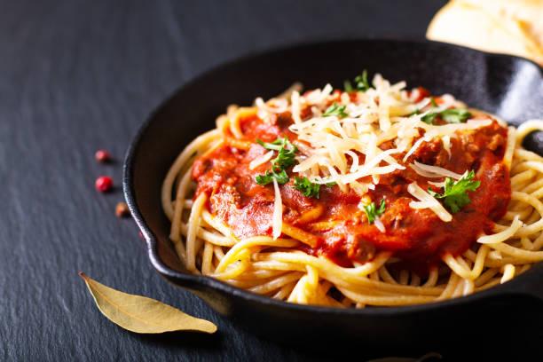boloñesa de espaguetis caseros de concepto de alimentos en hierro fundido en el fondo piedra pizarra negro con espacio de copia - pasta fotografías e imágenes de stock
