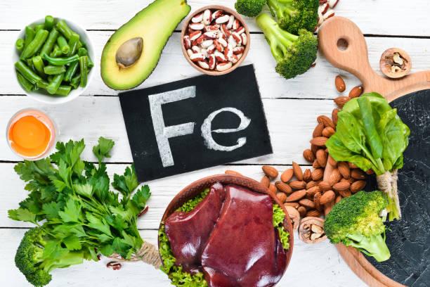 Alimentos que contenham ferro natural. Fe: fígado, abacate, brócolis, espinafre, salsa, feijão, nozes, em um fundo de madeira branca. Vista superior. - foto de acervo