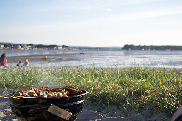 BBQ food cooking on the beach with family in background stock photo