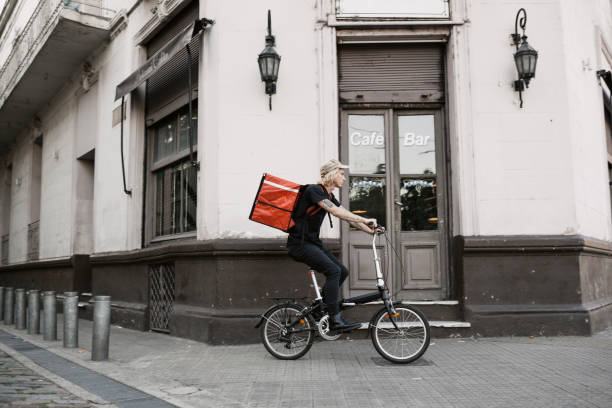 food courier cycling in the city - side hustle stock pictures, royalty-free photos & images
