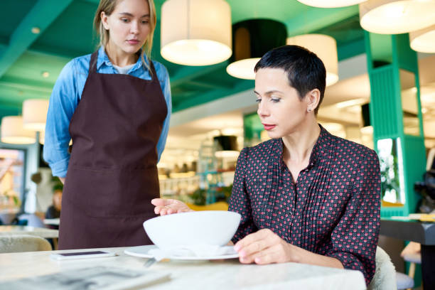 Food Critic Portrait of elegant woman  complaining about food quality and taste to young waitress in cafe critic stock pictures, royalty-free photos & images