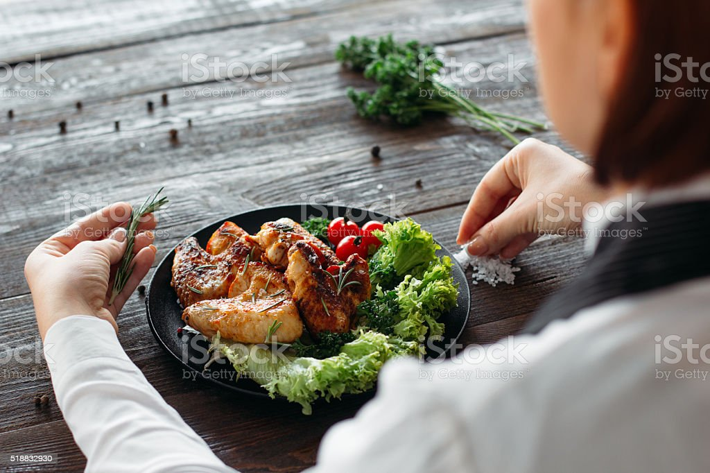 Food decoration. Chief adds spices and herbs stock photo