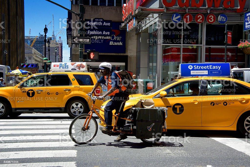 Food delivery bicyclist heading south on 7th Ave., Manhattan, NYC stock photo