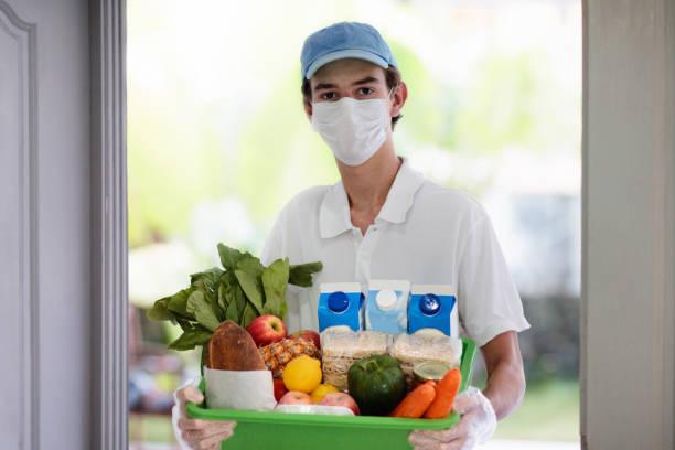 Lebensmittellieferung während des Virusausbruchs. Gesichtsmaske. – Foto