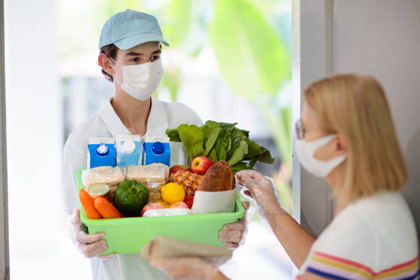 Food delivery during virus outbreak. Face mask. stock photo