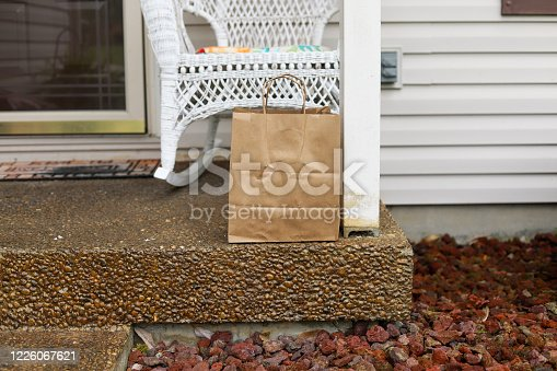 Food delivery in a brown paper bag on a porch of a home