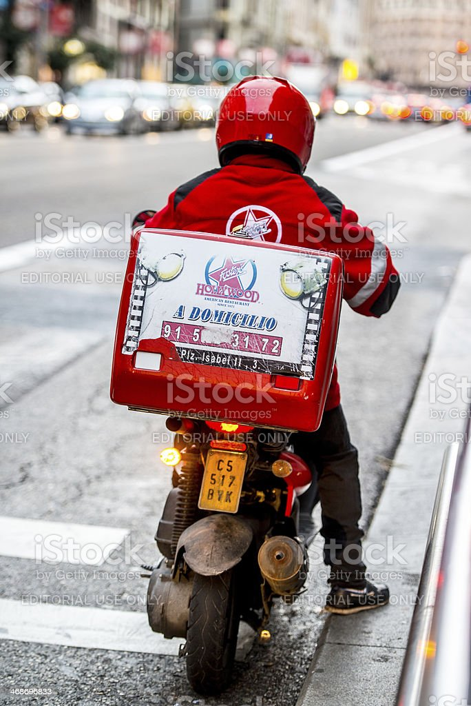 Food Delivery Motorcyclist on Madrid Street stock photo