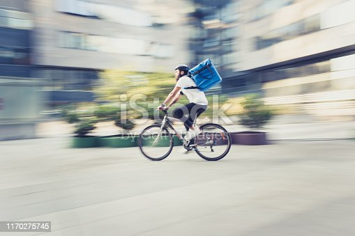 Food delivery on bicycle. Panning technique, blued motion