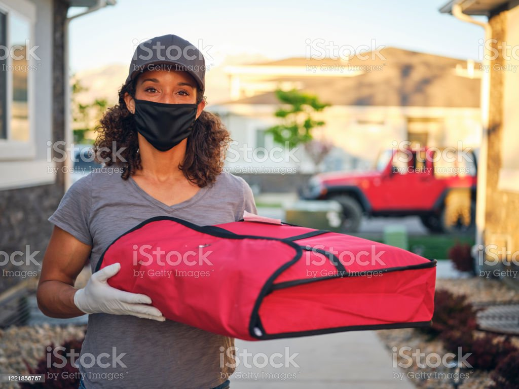 Food Delivery Person A young woman delivering takeout food to a home in the evening. 30-39 Years Stock Photo