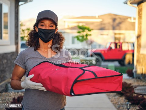 A young woman delivering takeout food to a home in the evening.