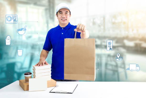 온라인 및 아이콘 미디어 주문에 대 한 음식 배달 서비스. 레스토랑 배경에 급행 배달을 위한 종이 봉지, 포장 용기 및 일회용 컵을 들고 파란색 유니폼 손에서 배달 남자. 스톡 사진