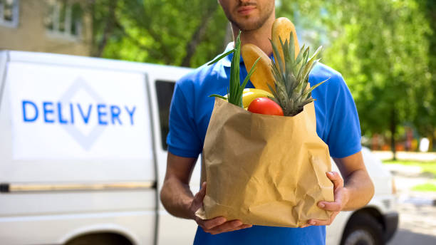 food delivery service, male worker holding grocery bag, express food order - delivery стоковые фото и изображения