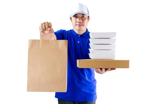 음식 배달 서비스 또는 온라인으로 음식을 주문합니다. 흰색 배경에 분리 된 식품 포장 용기와 종이 봉투를 들고 파란색 균일 한 손에 배달 남자. (클리핑 경로 포함) 스톡 사진