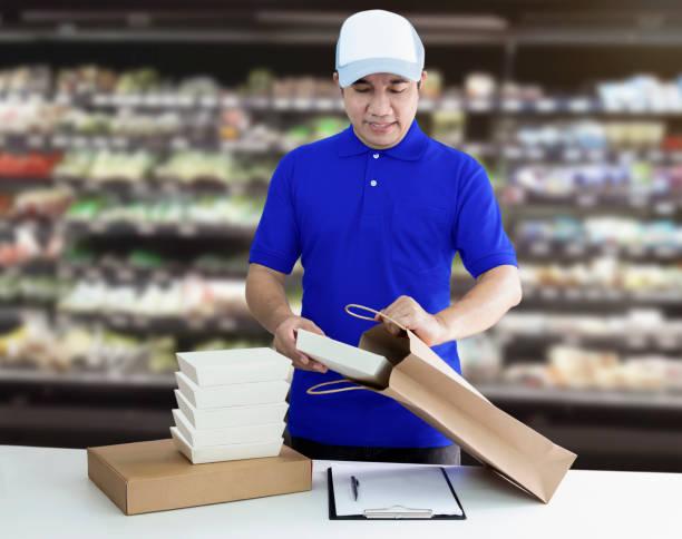 음식 배달 서비스 또는 온라인 쇼핑 주문 음식. 남자는 종이 봉투에 테이크 아웃 식품 용기에 넣고 슈퍼마켓 배경에 포장. 스톡 사진