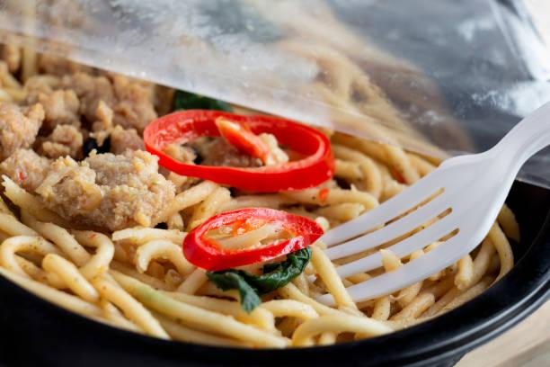 음식 배달 서비스 : 열린 집착 랩을 들고 여자 손과 나무 배경에 플라스틱 상자에 음식을 꺼내. 개념 온라인 주문은 택배를위한 준비 음식을 빼앗아. 스톡 사진