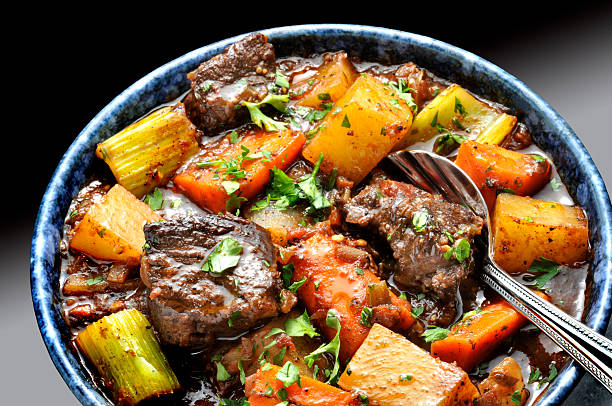 Food Dishes Beef stew  with carrots and potatoes n blue bowl with spoon. beef stew stock pictures, royalty-free photos & images