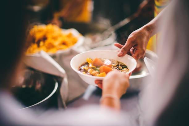 Lebensmittelspende an hungrige Menschen, arme Hände, die darauf warten, kostenlose Lebensmittel von Freiwilligen zu erhalten – Foto