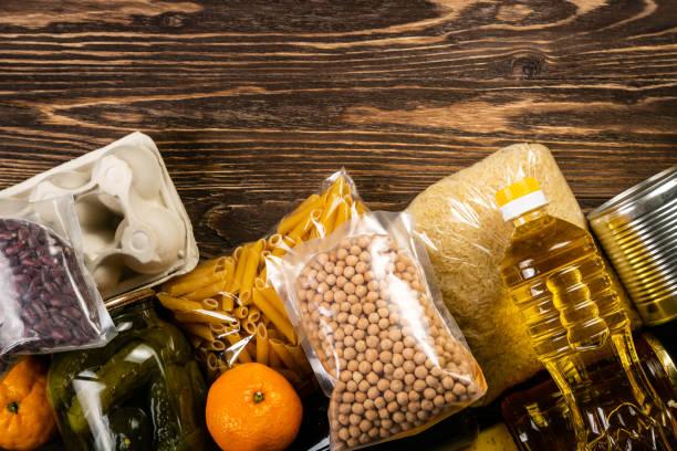 food donations in box in kitchen background - cassetta per le offerte foto e immagini stock