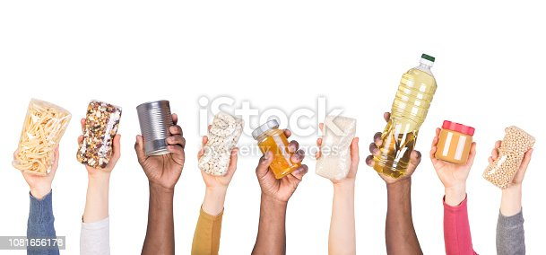 Food donations such as cooking oil, rice, peanut butter, pasta and canned food in hands isolated on white background