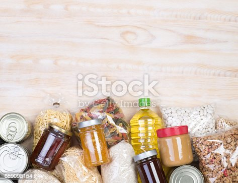 istock Food donations on wooden background 689098154