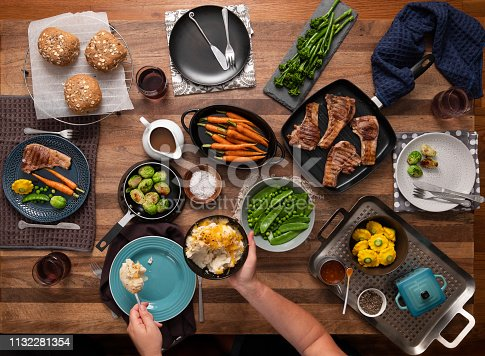 Woman serving food to 4 place settings at the table