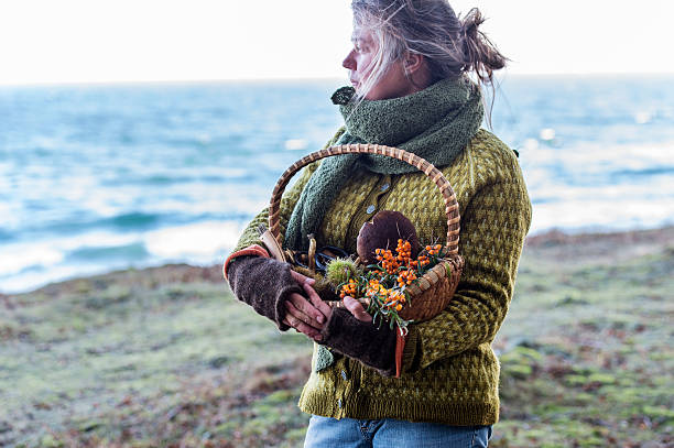 Food forager in traditional clothes by the sea Portrait of Food Forager holding her haul of foraged food in her basket whilst wistfully looking out to sea. Food foraging has become popular in recent years as chefs have turned to foraged food to produce local and seasonal menu's. Photographed in Denmark. foraging stock pictures, royalty-free photos & images