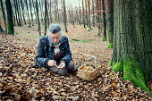 Portrait of a food forager picking and cleaning a mushroom she has found in the forest. Varieties include; chanterelles and hedgehog mushrooms. Food foraging has become popular in recent years as people have turned to foraged food to cook local and seasonally sourced food. Photographed on the island of Mon Denmark. Vertical format, she is wearing green coloured trousers a Fair Isle style sweater and a waxed jacket.