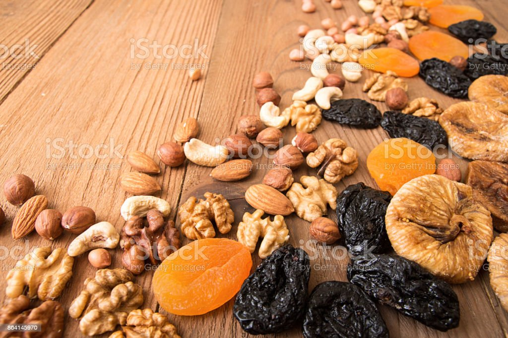 Food frame background with dried fruits and nuts: prunes, apricots, figs, hazelnuts, almond, cashew, walnut, peanuts over on old wooden background. Top view. Copy space. Rustic style. royalty-free stock photo