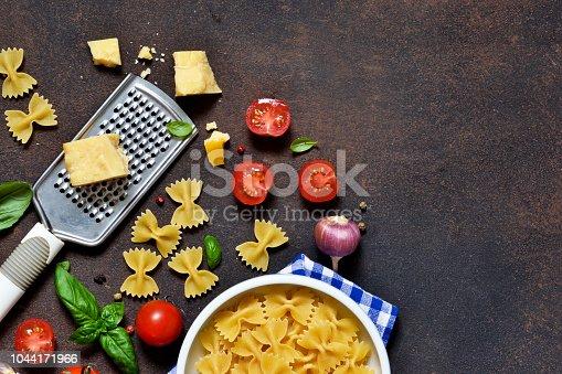 istock Food frame. Ingredients for pasta - cherry tomatoes, garlic, basil, Parmesan, top view. 1044171966