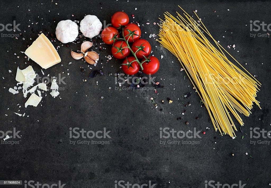 Cadre alimentaire. Pâtes et ingrédients. Merisier, des spaghetti pâtes aux tomates, ail et basilic - Photo