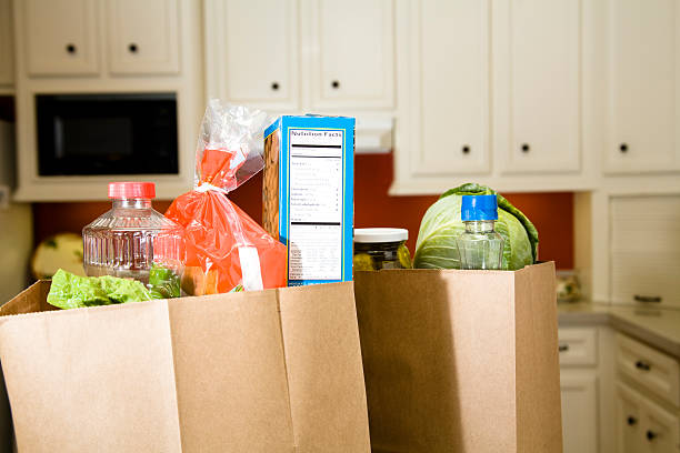 food:  grocery bags, sacks in home kitchen counter. - generic location stock pictures, royalty-free photos & images