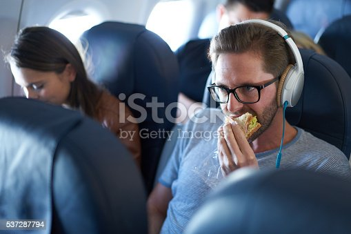 Man eating sandwich in economy class in airplane