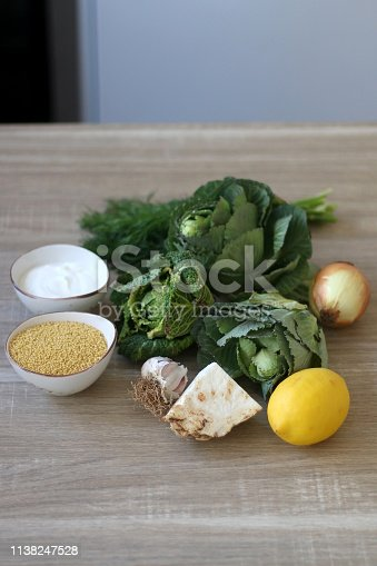Celery, cabbage, kale, onion, lemon, garlic, millet and yoghurt on a wooden table. Ingredients for a creamy soup.