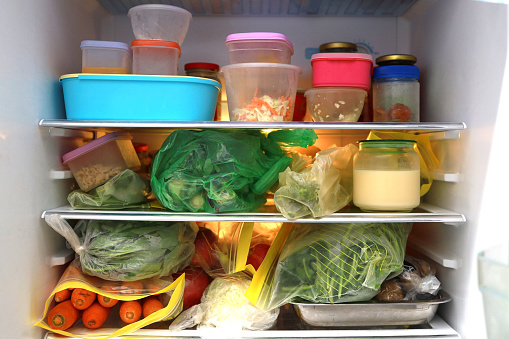 Plastic bag and container with food in refrigerator.