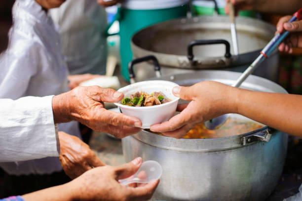 Nahrungsmittelbedarf der Armen in der Gesellschaft Hilfe bei Der Ernährung: Obdachlose holen Spenden von den Lebensmittelspendern in der Gesellschaft ab: Das Konzept des Bettlerproblems auf Erden – Foto