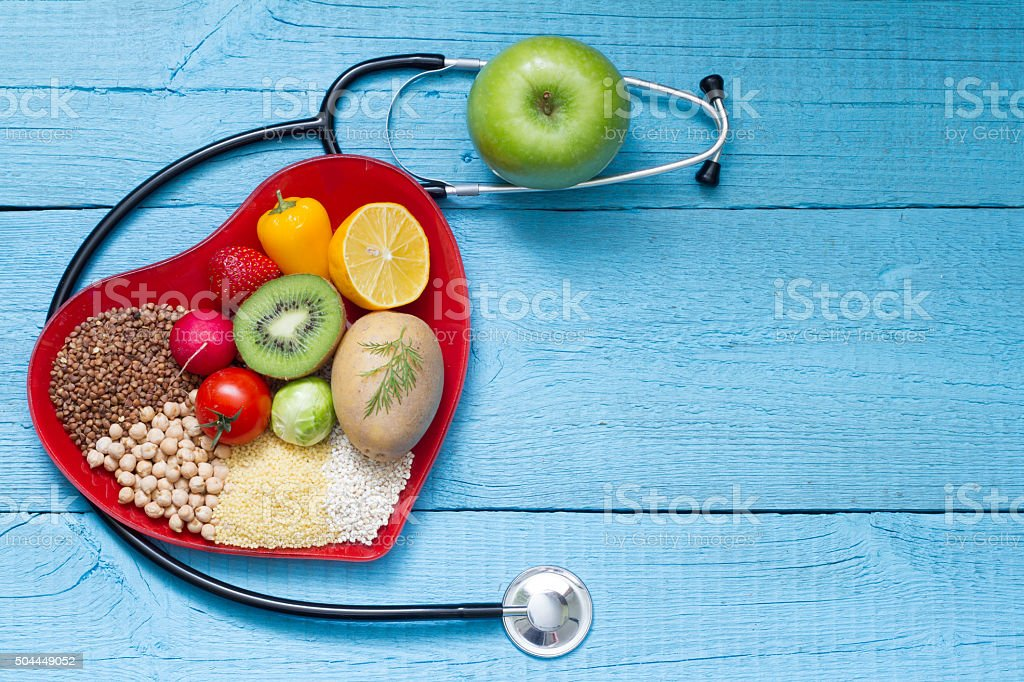 Food on heart plate with stethoscope cardiology concept Food on heart plate with stethoscope cardiology concept on blue boards Abstract Stock Photo