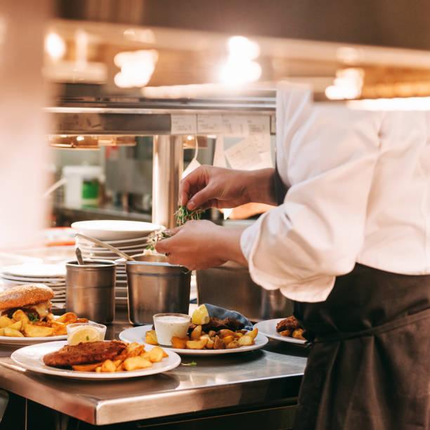 Essensbestellungen auf dem Küchentisch im Restaurant, Chefdekoration Schnitzel und Bratkartoffeln, traditionelle deutsche Platte – Foto