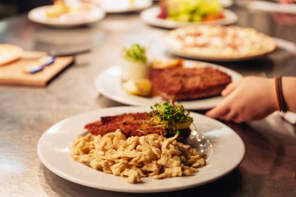 Essensbestellungen auf dem Küchentisch im Restaurant, Spétzle Nudeln mit Schnitzel, traditionelle deutsche Mahlzeit – Foto