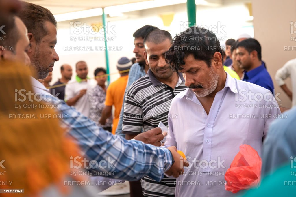 Food packages' distribution in mosque during Ramadan iftar meal. stock photo