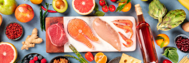 Food, panoramic top-down shot. Meat, fish, chicken and shrimps, vegetables and fruits, legumes, wine, cheese, overhead shot. Varied diet concept stock photo