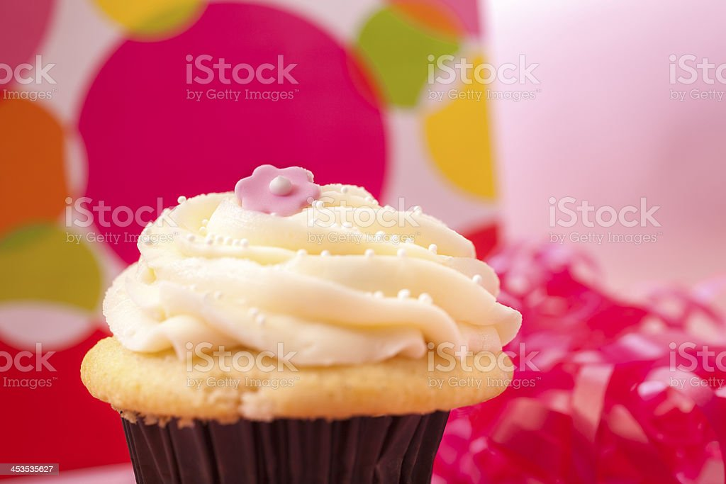 Food:  Pastel cupcake with gift and ribbon in background. royalty-free stock photo