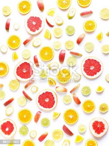 Food pattern of fresh fruit in a cut. Oranges, grapefruit, lemons, bananas, apples tangerines slices. Top view, flat lay. Citrus fruits background, wallpaper.