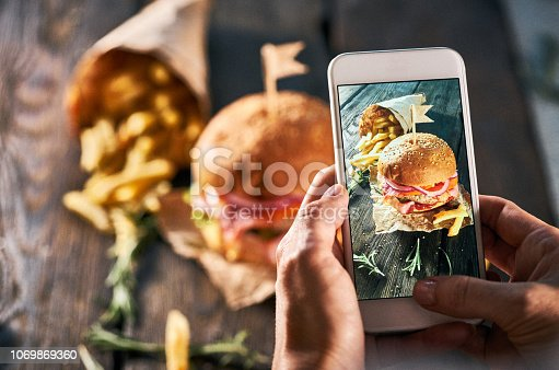 Food blogger taking photo of fresh burger for his personal blog