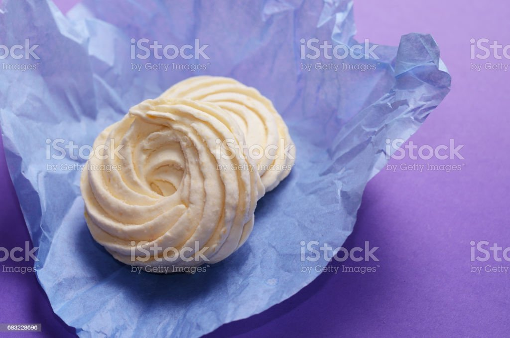 Food Photo of homemade zephyr, marshmallow in violet wrapping paper. Healthy sweet dessert on a pink background. royalty-free stock photo