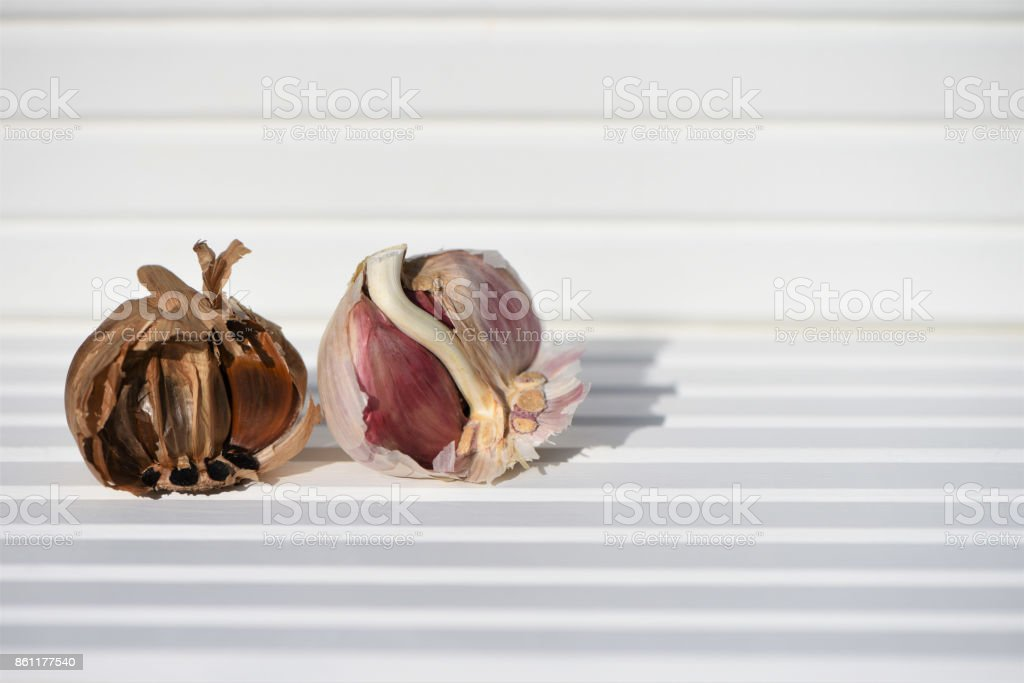 food photography image of black and white garlic bulbs and cloves in sunlight on white wood backgorund and taken on South coast England UK stock photo